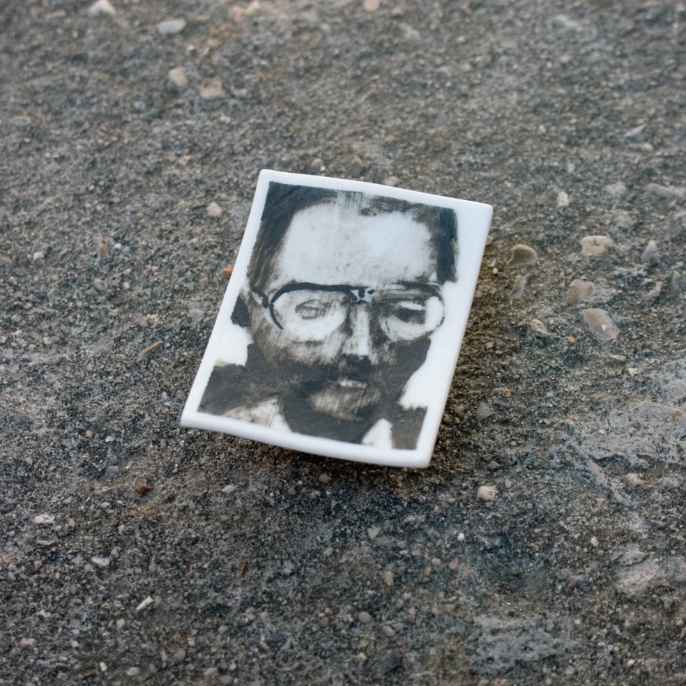236 - Phossil 106 - man with glasses (2015) - 5.7cm x 4.3cm x 0.3cm approx.- hand-painted with pigment on porcelain, fired twice up to 1280cº